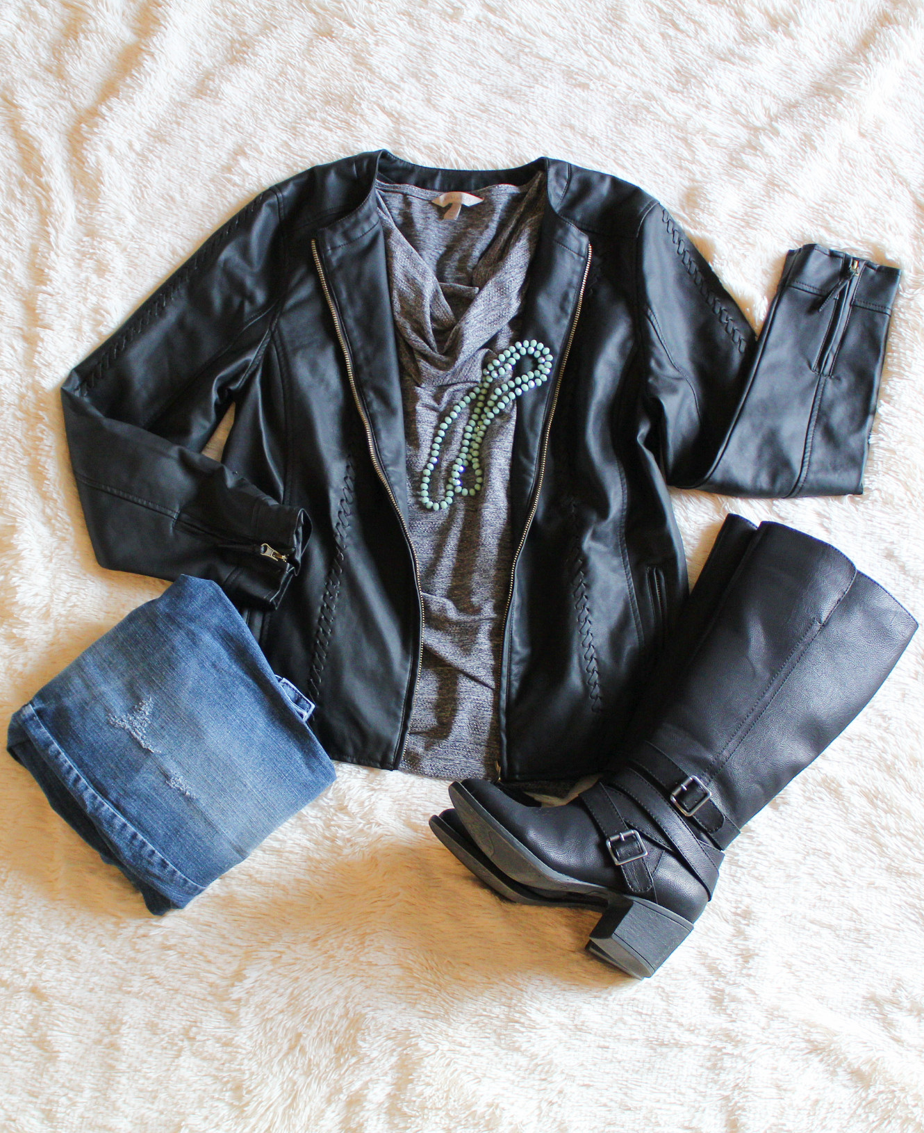 A flay lay featuring a faux leather jacket, silver and balck top, jeans and black boots. Winter Outfit/Fashion Over 40/Dressed in Faith fashion